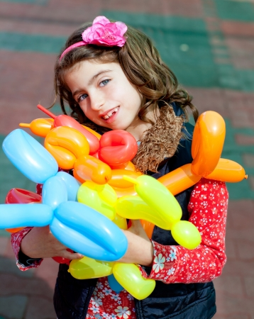 twisting: balloon twisting art children happy girl after workshop with many shapes Stock Photo