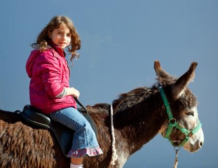 donkeys: donkey mule with kid little girl riding happy smiling on blue  Stock Photo