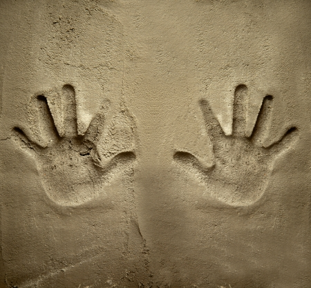 both: both hands print on cement mortar wall with shadow relief Stock Photo