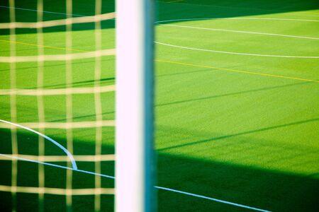 goal post: Green soccer net detail with sport grass field background Stock Photo