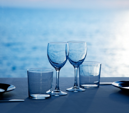 Glass dish cups and glasses on blue sea background photo