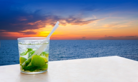 Mojito cocktail on a sunset beach golden red sky sunrise photo