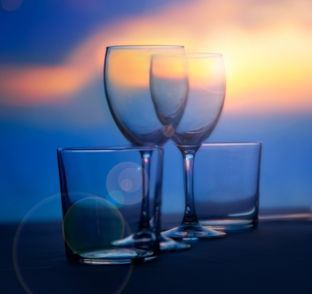 dinner cruise: Dish of cups and crystal transparent glasses on a sea sunset table