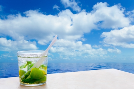 Mojito cocktail drink in summer blue calm sea and sky clouds photo