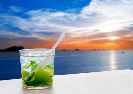 beach cruiser: Ibiza cala Conta Conmte sunset with Mojito drink cocktail Stock Photo