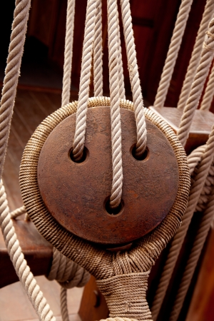 pulley: Ancient wooden sailboat pulleys and ropes detail