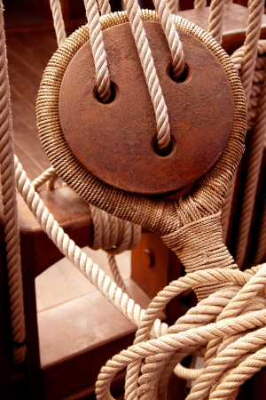 rigging: Ancient wooden sailboat pulleys and ropes detail