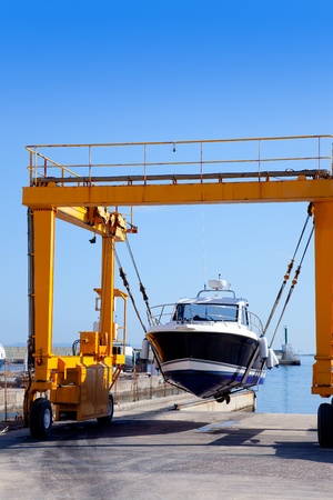 hull: crane travelift lifting a boat on blue sky day in balearic islands