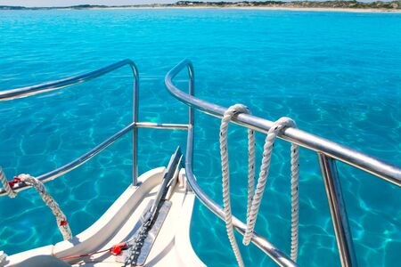 Boat in Formentera island transparent water on llevant beach photo