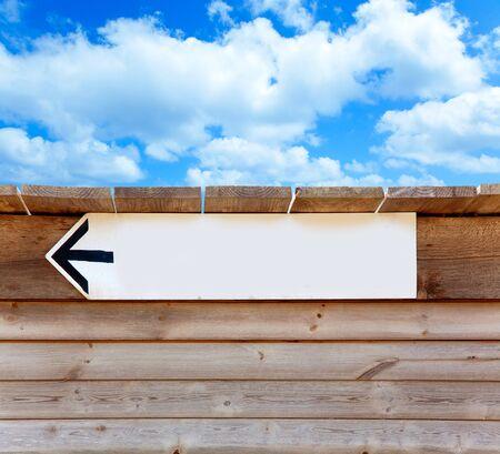 aged wood arrow direction sign on summer blue sky photo