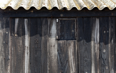 Aged black wood with wavy roof in balearic beach in Spain photo