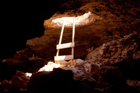 Barbaria cape cave hole with rustic ladder on wood and the light in out hole photo