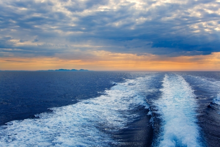 motorboat: Blue sea with prop wash wake and Ibiza Island in horizon on sunrise
