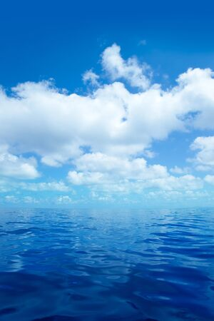 Blue calm sea water in offshore ocean with clouds mirror surface photo