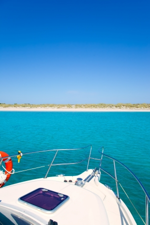 Boat anchored in Formentera Espalmador in turquoise Balearic island photo