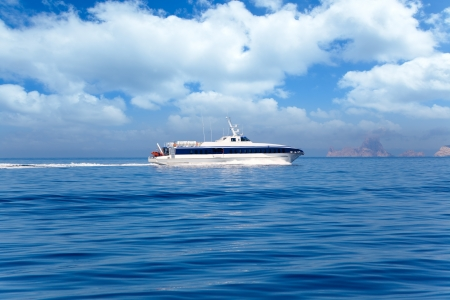 vedra: Boat ferry cruising Ibiza to Formentera with Es Vedra in background Stock Photo
