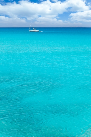 Balearic mediterranean turquoise sea with sailboat under blue sky photo