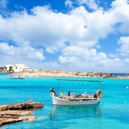 paisaje mediterraneo: Els Pujols playa de Formentera con barco de pesca tradicional en día de verano Foto de archivo