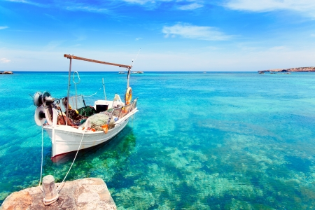 Els Pujols beach in Formentera with traditional fishing boat in summer day photo