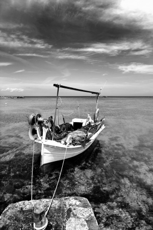 Els Pujols beach in Formentera with traditional fishing boat in black and white photo