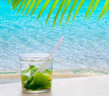 Mojito cocktail with peppermint leaves and lemon in tropical perfect beach and palm leave photo