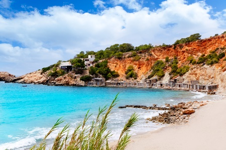 Cala d Hort Ibiza beach with traditional wood boat mooring in Balearic island