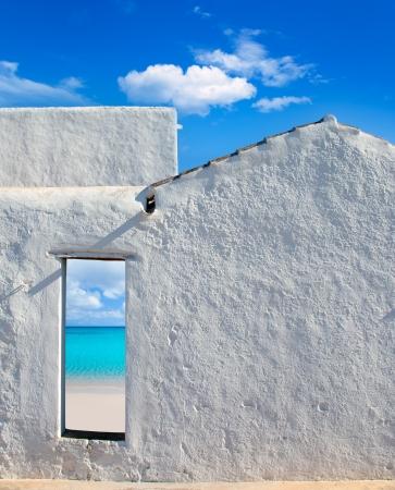 whitewashed: Balearic islands idyllic turquoise beach view through whitewashed house open door