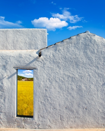 open country: Balearic islands golden wheat field view through whitewashed house open door