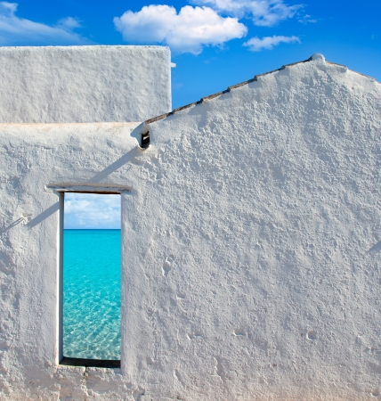 Balearic islands idyllic turquoise beach view through whitewashed house open door photo