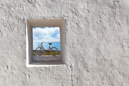 view through: Balearic islands beach and bicycle view through whitewashed house window Stock Photo