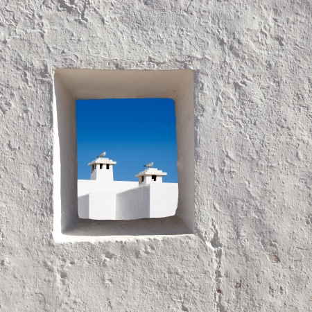 through the window: Balearic islands white chimney with seagull view through whitewashed house window