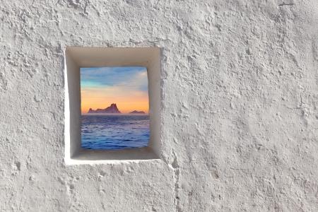 view through: Balearic islands Es Vedra sunset view through whitewashed window Stock Photo