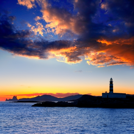 Ibiza island sunset with freus lighthouse and Es Vedra in background photo