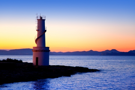 Ibiza island sunset of Es Vedra and La  Savina lighthouse in Formentera photo