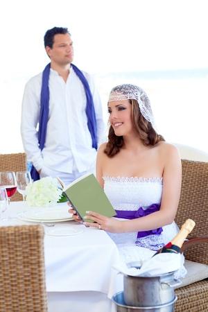 mesa para banquetes: Pareja en el d�a de la boda con el libro de lectura de la mujer en la mesa del banquete
