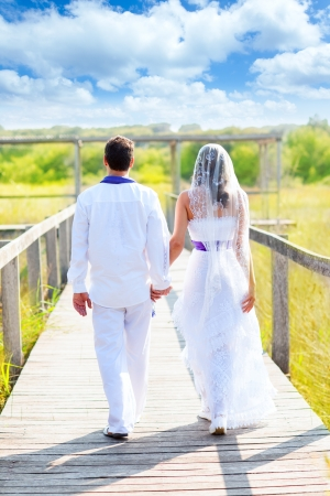 Couple happy in wedding day walking in outdoor rear view photo