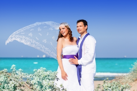purple dress: Couple in wedding day on beach sea with wind on veil