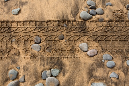 4x4: car tire footprint in a sand and rolling stones beach texture Stock Photo