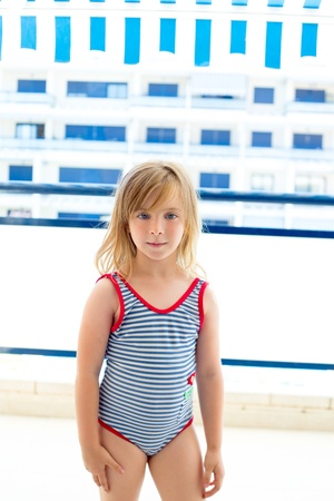 child swimsuit: Blond kid girl with summer swimsuit in blue apartment balconade