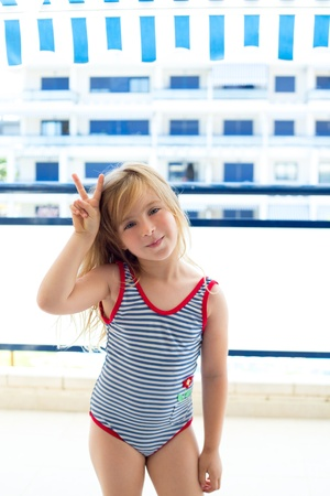 bathing costume: Blond kid girl with summer swimsuit with hands victory sign smiling Stock Photo