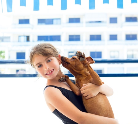 Brunette kid girl with summer swimsuit playing with dog in apartment photo