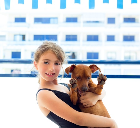 little girl swimsuit: Brunette kid girl with summer swimsuit playing with dog in apartment