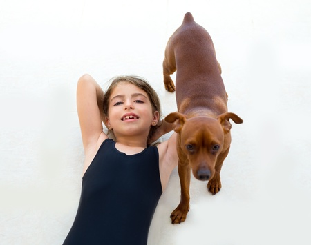 Brunette kid girl with summer swimsuit playing with dog lying on floor photo