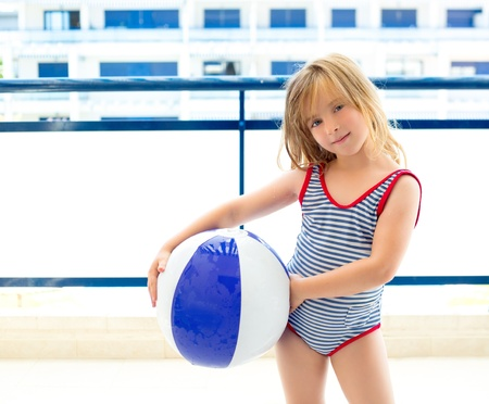 Blond kid girl with swimsuit with summer blue ball in balconade photo