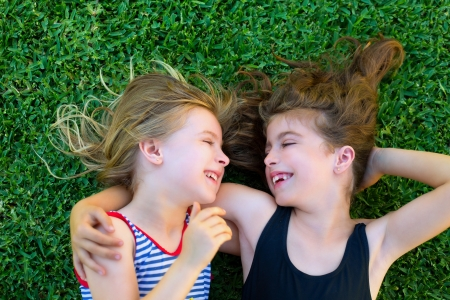 mischief: Blond and brunette sisters kid girls smiling lying on garden grass