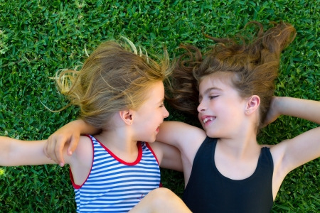 Blond and brunette sisters kid girls smiling lying on garden grass photo