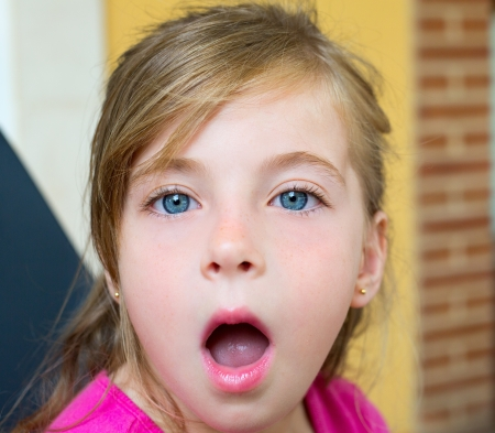 mouth open: Blond girl with surprised gesture face portrait and open mouth