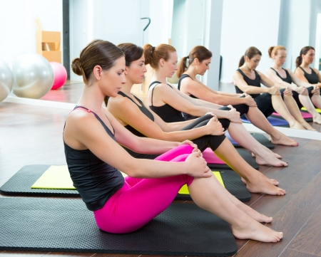 ball stretching: Aerobic Pilates personal trainer woman at gym group class in a row Stock Photo