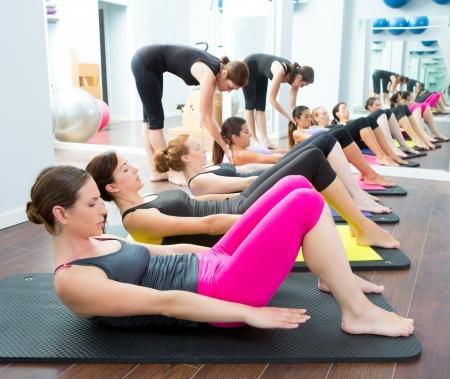 abdominal fitness: Aerobic Pilates entrenador personal en un gimnasio de clase de grupo en una fila