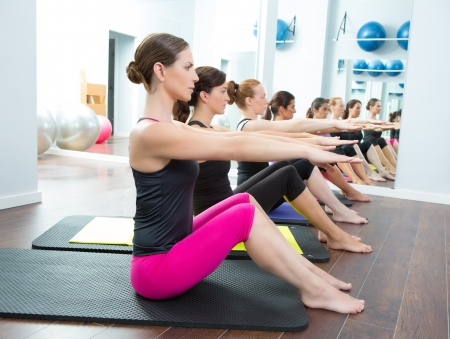 limber: Aerobic Pilates personal trainer in a gym group class in a row